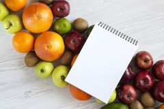 Set of raw fruits with notebook on white wooden background. Healthy food concept, top view. Flat lay. Summer background Stock Photos