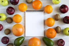 Set of raw fruits with notebook on white wooden background. Healthy food concept, top view. Flat lay. Summer background Royalty Free Stock Photos