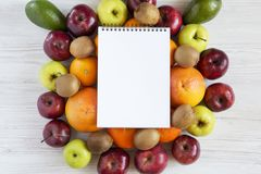 Set of raw fruits with notebook on white wooden background. Healthy food concept, top view. Flat lay. Summer background Royalty Free Stock Photo