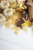A set of raw pasta on a wooden table Royalty Free Stock Image
