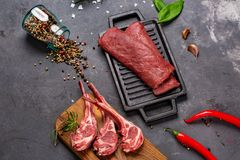 Set of Raw uncooked black angus beef tomahawk steaks on bones and veal tenderloin served with chilli and peppercorns. Rustic style stock image