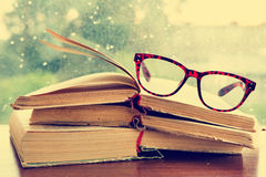 Set of reading glasses and books over the window. Reading glasses and books over the window stock image