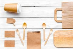 Set of recycle brown paper bag, disposable tableware cup, spoon, fork, notebook on white wooden background top view stock photography
