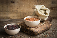 Set of red, black and mixed rice on an old wooden background Royalty Free Stock Photos