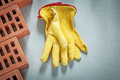 Set of red construction bricks safety gloves on concrete surface. Building concept Stock Images