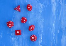 Set of red dices for rpg, board games, tabletop games or dnd on blue background. Closeup Royalty Free Stock Images