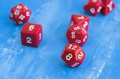 Set of red dices for rpg, board games, tabletop games or dnd on blue background. Closeup Royalty Free Stock Photo