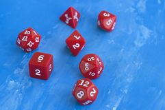 Set of red dices for rpg, board games, tabletop games or dnd on blue background. Closeup Stock Images