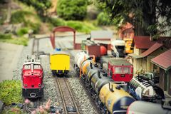 Set of red electric model railway locomotive and layout with a station and whole scene with features. royalty free stock photos