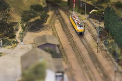 Set of red electric model railway locomotive and layout with a station and whole scene with features. stock photos