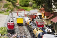 Set of red electric model railway locomotive and layout with a station and whole scene with features. royalty free stock photo