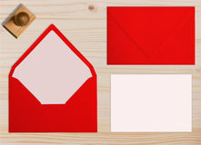 Set of red envelopes, with rubber stamp and card. Collection on wooden background. Royalty Free Stock Photos