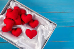 Set of red heart made from velvet fabric lay in white box with white satin on vintage blue table wood. Royalty Free Stock Images