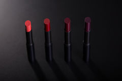 Set of red lipsticks on black background Royalty Free Stock Photography