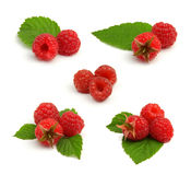 Set of red raspberry heaps with leafs on white. Set of red ripe raspberry heaps with green leafs on white background Stock Photos