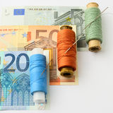 Set for repair. Concept. Renovation of European financial system. Colored thread and a needle for repair of Euro Royalty Free Stock Photos