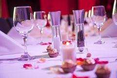 Set restaurant table for special occasion. With lit candles and chocolates Royalty Free Stock Image