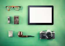 Set of Retro hipster mock up. Laptop, old camera, tablet and smoke pipe on green background. Filtered image Stock Photos