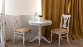 A set of round table with flowers and two elegant chairs in a classic interior. Vintage style royalty free stock photos