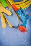 Set of rubber garden hose spray nozzle protective gloves shovel. On metallic background gardening concept royalty free stock photos