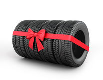 A set of rubber tires with ribbon and bow. Royalty Free Stock Image