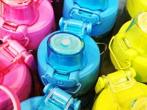 A set of safe reusable bottles with water from stainless steel in pink, yellow and blue. Stock Image