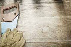Set of safety gloves stainless handsaw on wood board constructio Stock Photos