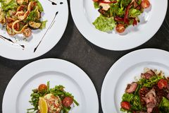 Set of salads. With meat, seafood and fresh vegetables on black background Stock Photos
