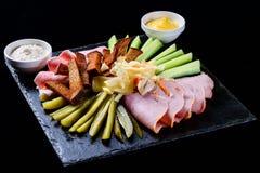 Set of salami snacks, ham, sausage and fermented cucumbers royalty free stock photos