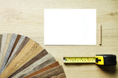 Set of samples of floorboard with measuring tapeand pencil and n. Samples of laminate and vinyl floor tile on wooden Background Royalty Free Stock Image