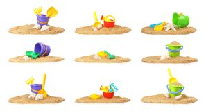 Set of sand piles with different plastic toys on white background. Beach accessories royalty free stock images