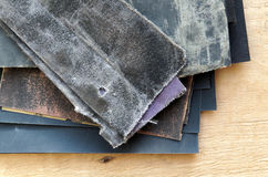 A set of sandpaper for wood and metal. Against the sheet of plywood Royalty Free Stock Photo