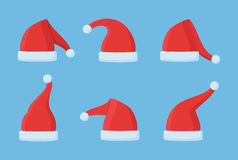 Set of Santa Claus red hats  on blue background. Christmas elements. Flat style vector illustration Royalty Free Stock Photos