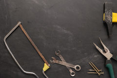 Set of saw, plier, screw and hammer. Tools over a wood panel. To Stock Photo