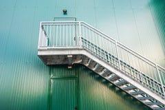 Set schodki i drzwi w zieleni malowaliśmy ścianę w stronę przemysłowy budynek zdjęcia royalty free