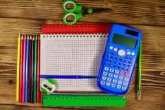 Set of school stationery supplies. Blank notepad, calculator, rulers, pencils, pens, scissors and sharpener on wooden desk. Top view stock photography
