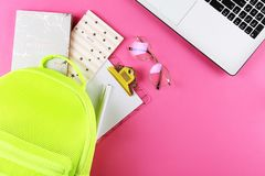 Set of school supplies on paper textured background. Hipster neon green textile backpack, surrounded with school supplies. Back to school concept. Lots of stock images