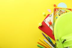 Set of school supplies on paper textured background. Hipster neon green textile backpack, surrounded with school supplies. Back to school concept. Lots of royalty free stock image