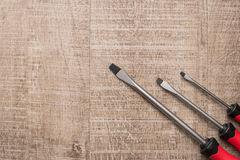 Set of screwdrivers. Tools over a wood panel.  Stock Photo