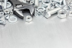 Set of screws and bolts with adjustable wrench on scratched meta Stock Photos