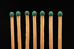 Set of seven green wooden matches on black background Stock Photos