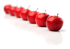 A set of seven red plastic apples in a row Stock Photo