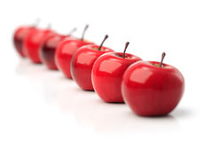 A set of seven red plastic apples in a row Royalty Free Stock Photos