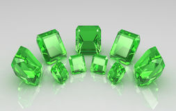 Set of seven round emerald on glossy surface Royalty Free Stock Photography
