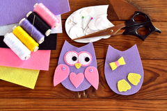 Set for sewing a felt owl, paper templates, felt sheets, scissors, thread, needle, pins on a brown wooden background Stock Images