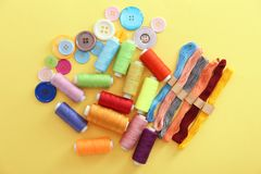 Set of sewing and mouline threads. With buttons on color background Stock Photos