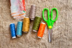 Set for sewing: scissors, multi-colored threads, needles, fabric royalty free stock image