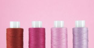 Set of sewing threads beautiful color red, crimson, pink and lilac on pink background with space for text stock photo