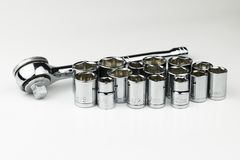 Set of shiny, chrome Metric and SAE sockets with ratchet. A shiny, silver, chrome socket wrench set with both SAE fractional sockets and metric sockets in royalty free stock images