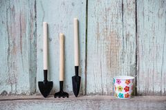 A set of shovels and a rake on a wooden fence with a small empty bucket.  stock photos